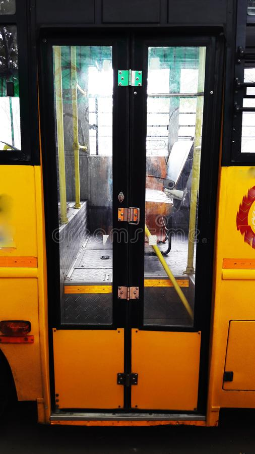 Yellow bus closed door closeup view. Wheel, auto, adult, public, interior, steering, transport, car, tour, rapid, cab, tourism, male, profession, school royalty free stock photos