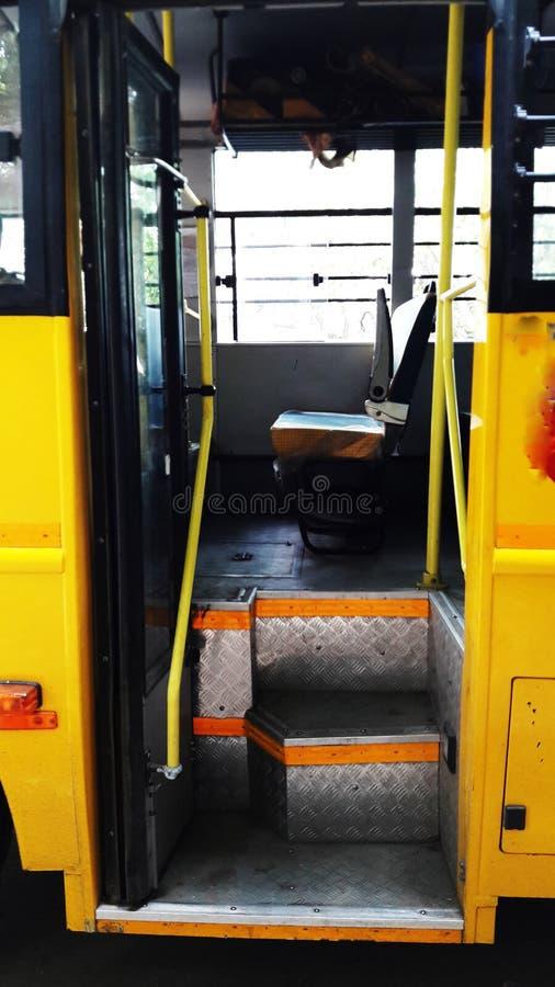 Yellow bus open door closeup image. Wheel, auto, adult, public, interior, steering, transport, car, tour, rapid, cab, tourism, male, profession, school, travel royalty free stock photo