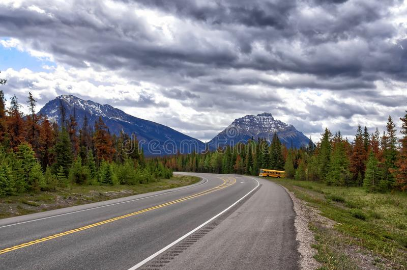 Yellow bus on the road among the Rocky mountains.  picturesque cloudy sky. Beautiful views of Icefields Parkway royalty free stock image