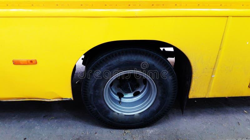 Yellow bus tyre closeup view. Wheel, auto, adult, public, interior, steering, transport, car, tour, rapid, cab, tourism, male, profession, school, travel stock image