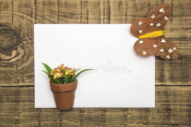 Yellow butterfly and flowers with white paper, copyspace on a wooden background. concept of summer, greeting card, banner, flyer. stock image