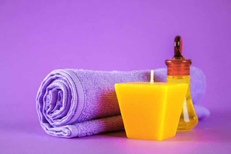 Yellow candle and aroma oil, violet towel on purple background. Spa. stock photo