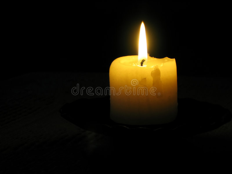 in a dark dark room yellow candle in a dark room royalty free stock photography