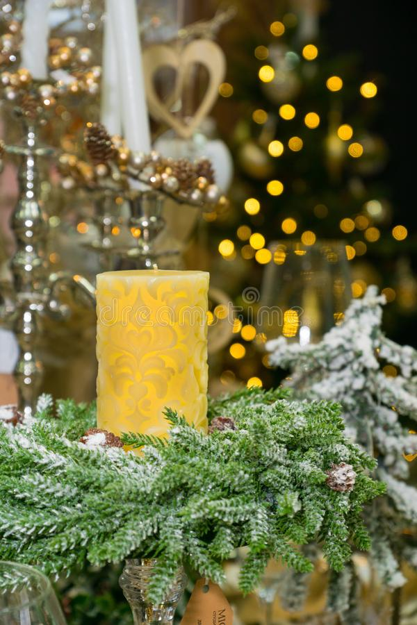 Yellow candle over xmas tree with lights stock photos