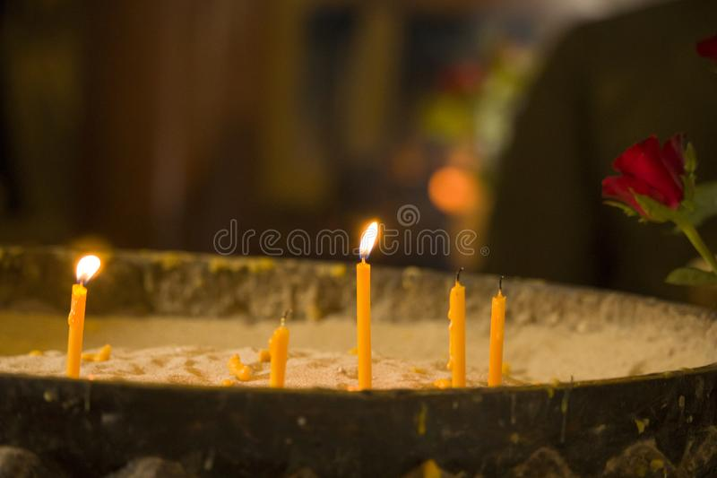 Yellow candle on the pot with sand. stock photography