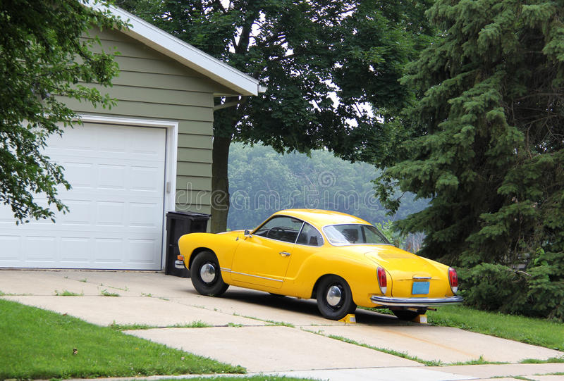 Yellow car on the driveway. Summer view with old fashion yellow car on the driveway and closed garage door royalty free stock photo