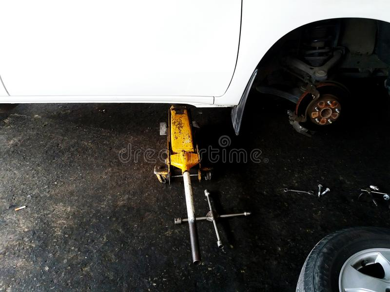 Yellow car lift jack lifting white car during fixing, maintenance or change new brake with half of tire at garage royalty free stock photography