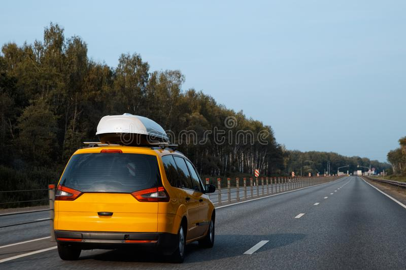 The yellow car with rooftop cargo carriers is driving along the summer. Highway on a journey royalty free stock photos