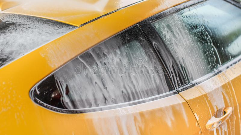 Yellow car washed in self serve carwash, shampoo spraying from hose to roof, streams of foam flowing down the window.  royalty free stock photos