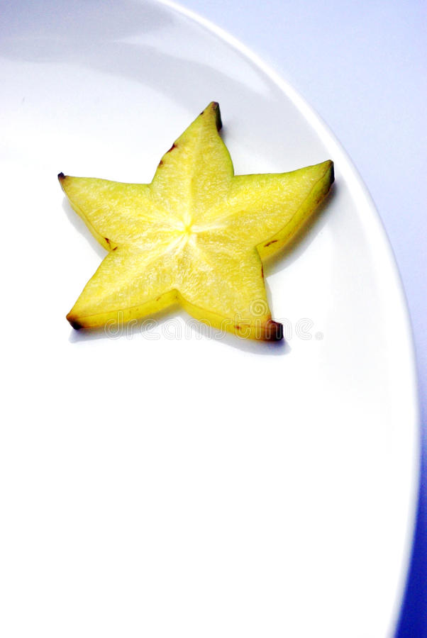 Yellow carambola slice on white plate stock photos
