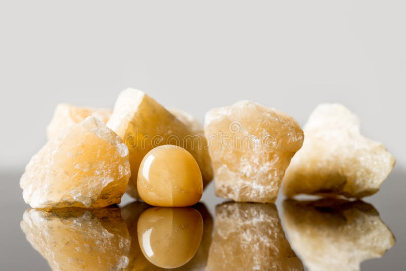 yellow carnelian, uncut and tumble finished, concept crystal healing royalty free stock images