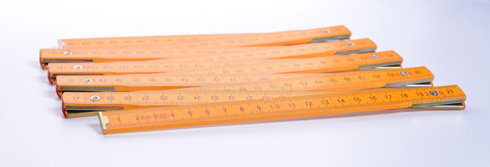 Yellow carpenter`s ruler. On a white background royalty free stock image
