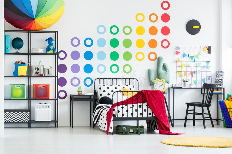 Kid`s bed in rainbow bedroom. Yellow carpet on the floor and red blanket on kid`s bed in rainbow bedroom with toys and chair royalty free stock photo