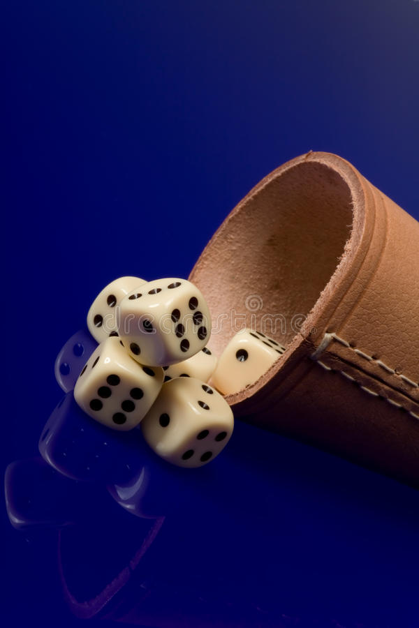 Yellow casino dice with cup stock photography