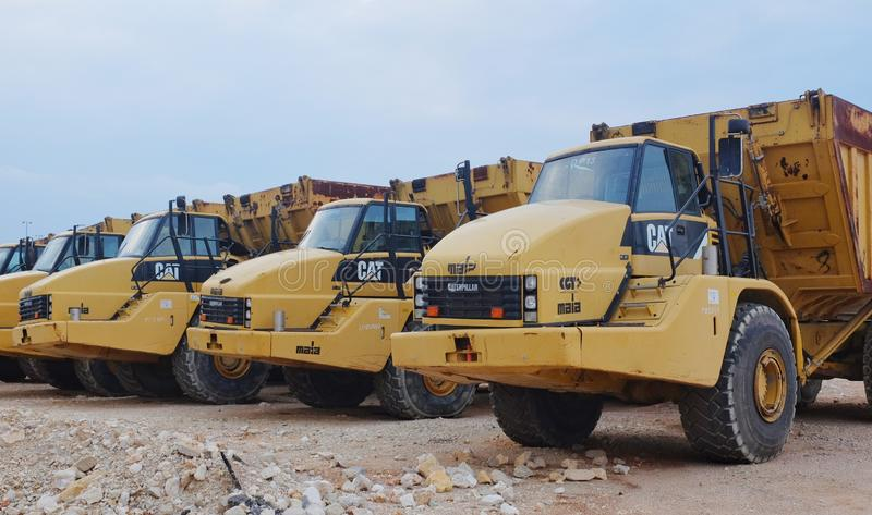 Caterpillar Trucks. A yellow Caterpillar truck among other construction vehicles royalty free stock photo