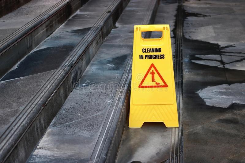 Yellow caution cleaning progress sign on the floor outdoors.  royalty free stock photography