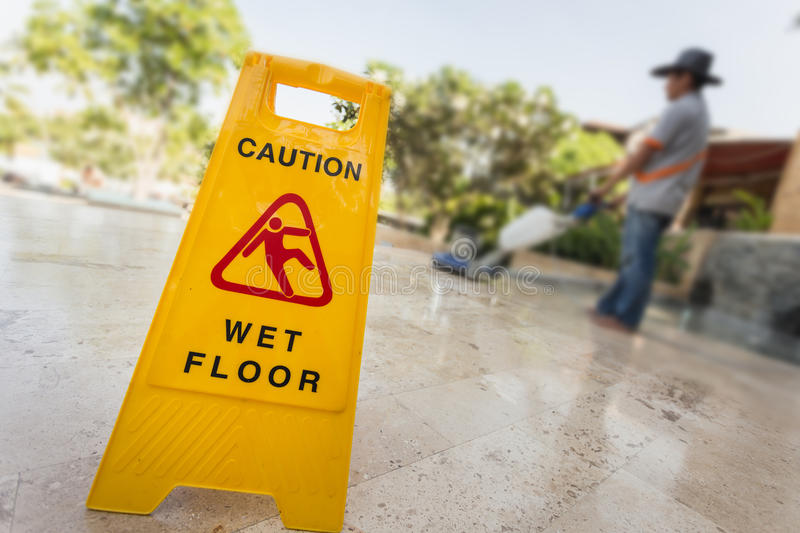 Yellow caution sign and blur of man doing floor polishing. Close up yellow caution sign and blur of man doing stone floor polishing stock photography
