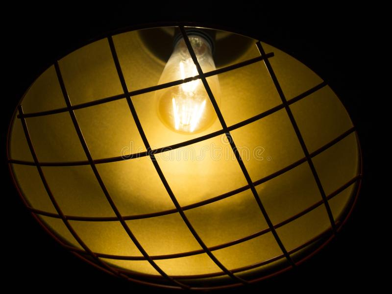 Yellow ceiling lamp with iron wire protection on.  royalty free stock photography