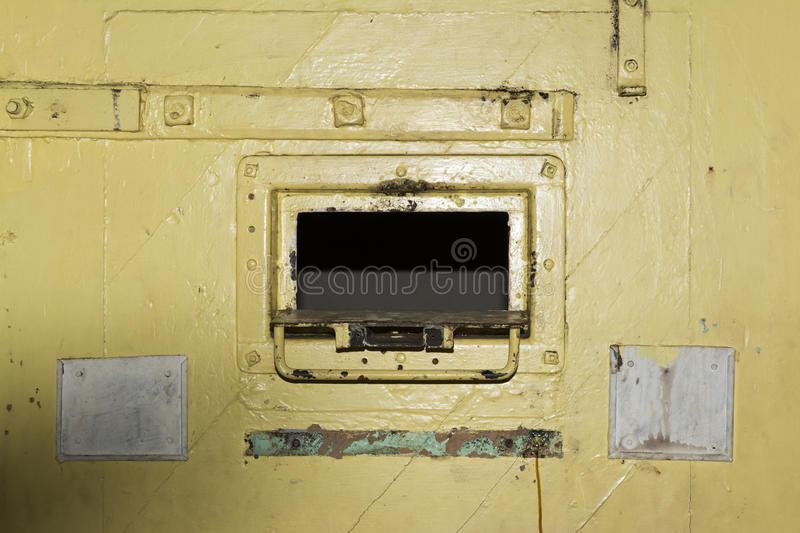 Yellow Cell Door Hatch, Adelaide Gaol, Adelaide, South Australia. Adelaide, South Australia - August 14, 2016: Open cell door hatch of a remand cell at the old royalty free stock photography