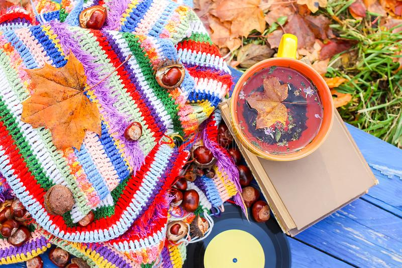 Yellow ceramic cup of herbal tea and vintage vinyl records on aged wooden background with bright handmade crocheted plaid, fall. Autumn composition of yellow royalty free stock images