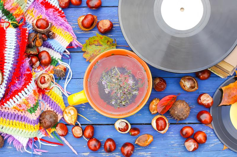 Yellow ceramic cup of herbal tea and vintage vinyl records on aged wooden background with fall autumn leaves and chestnuts. Acoustic, aesculus, autumnal stock photo