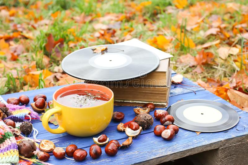 Yellow ceramic cup of herbal tea and vintage vinyl records on aged wooden background with fall autumn leaves and chestnuts. Acoustic, aesculus, autumnal royalty free stock photography