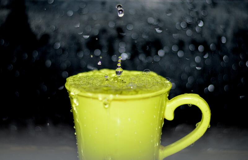 Yellow Ceramic Mug With Water Droplets in Time Lapse Photography stock images