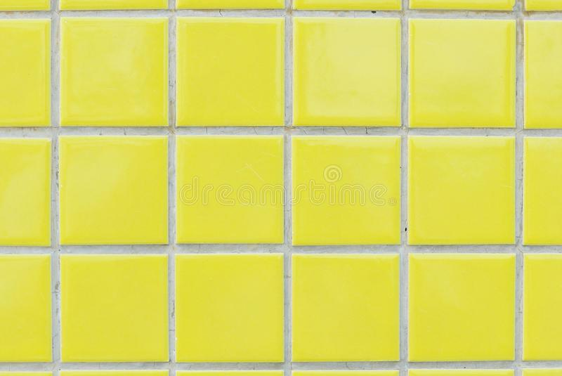 Yellow ceramic wall and floor tile abstract background. Square bathroom mosaic texture pattern design architecture tiled decorative pool decoration surface royalty free stock image
