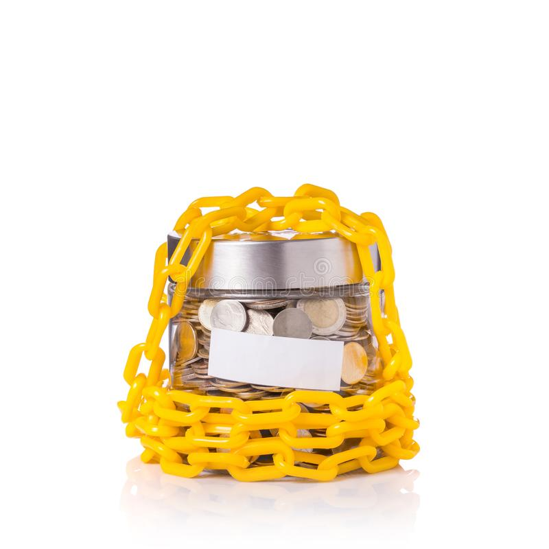Yellow chain lock around clear glass jar of Thai coin (baht). St royalty free stock images