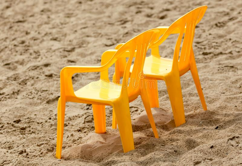 Yellow chairs in the sand on the beach royalty free stock photos