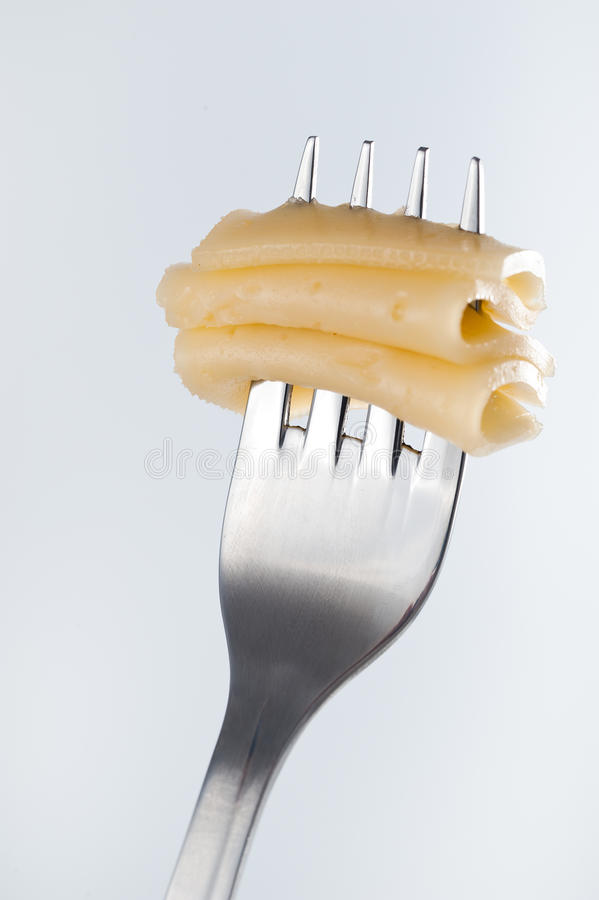 Yellow cheese on a fork royalty free stock photography