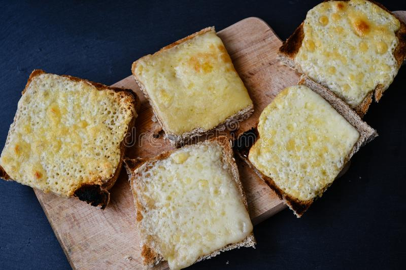 Cheese toast. Yellow cheese hot toast on wooden background stock photos