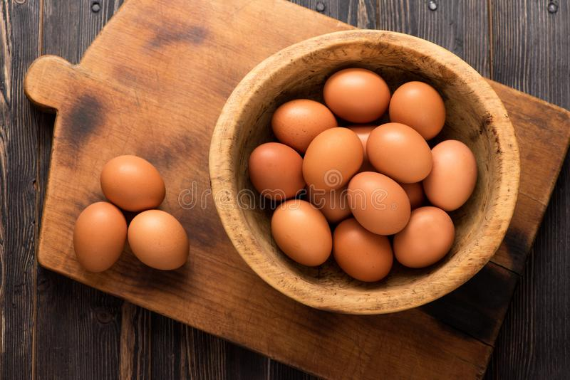 Yellow chicken eggs in a wooden bowl on a wooden background royalty free stock photography