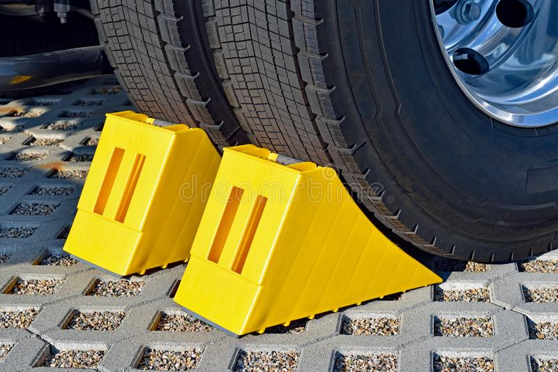 Yellow chocks at the wheel of a parked truck stock photos