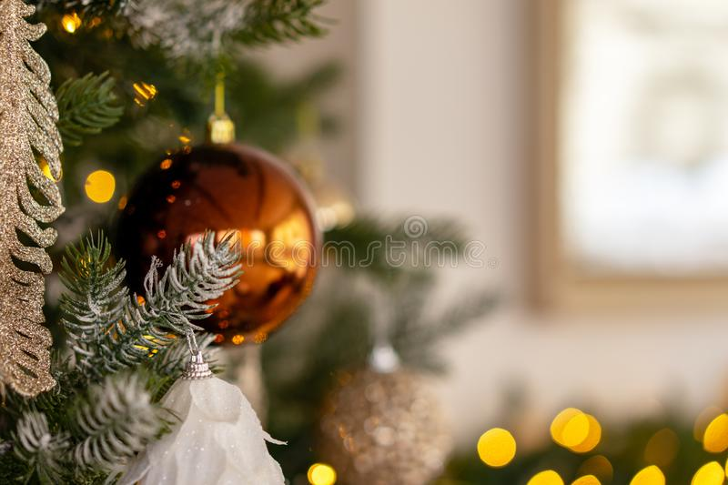 Yellow Christmas ball on a Christmas tree with a garland on the background of a window royalty free stock photography