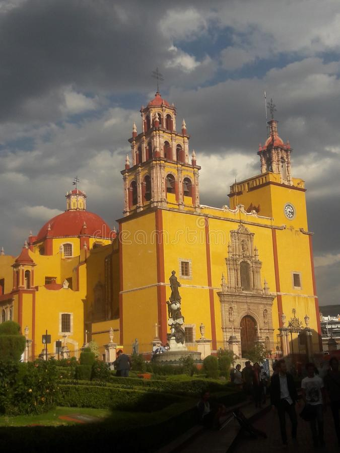 Yellow Church on a stormy day in Guanajuato Mexico. Catholic, religion, worship, tourism, travel, rain, cloudy, tower, dome, clock, christianity, colonial royalty free stock image