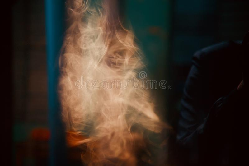 Yellow cigarette smoke unique blurry photo. Beautiful yellowish smoke of cigarette isolated unique blurry photo royalty free stock images