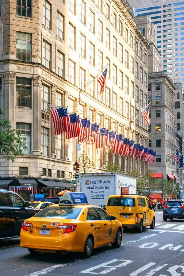 Yellow city cabs in the streets of Manhattan with american flags on building in background stock photo