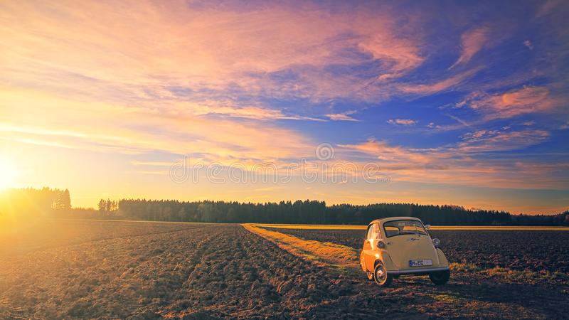 Yellow Classic Car Parked on Field Under Cloudy Sky at Golden Hour royalty free stock photo