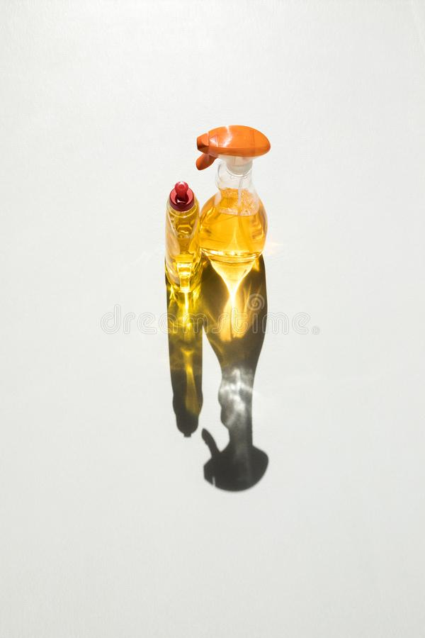 Yellow cleaning fluids. High angle view of plastic bottles with yellow cleaning fluids on white stock photos