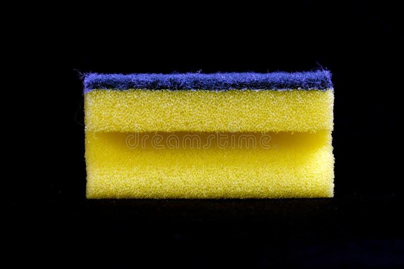Yellow cleaning sponge black background stock photos
