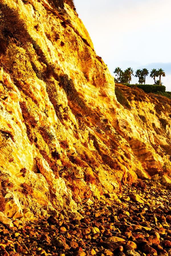 Yellow cliffside from reflected sunrise light. rocks on shore stock photo