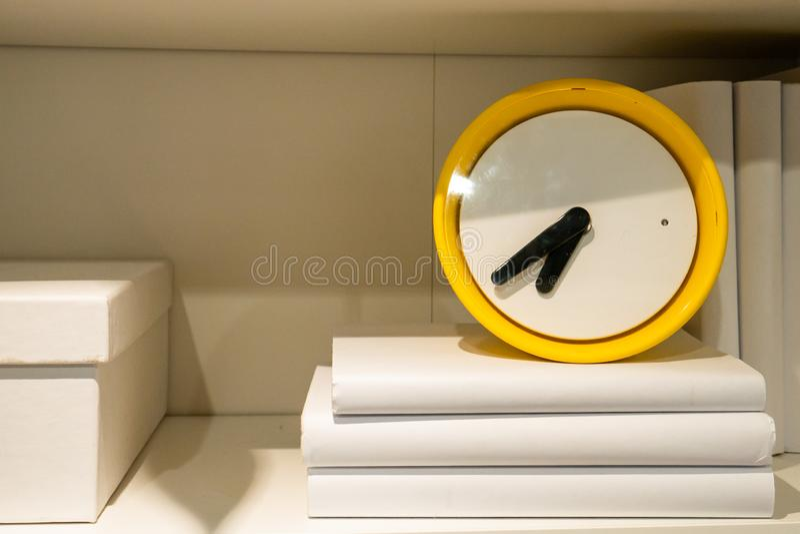 Yellow clock on the shelf. Copyspace. White books. Yellow clock on the shelf. Copyspace. Lots of white books royalty free stock image