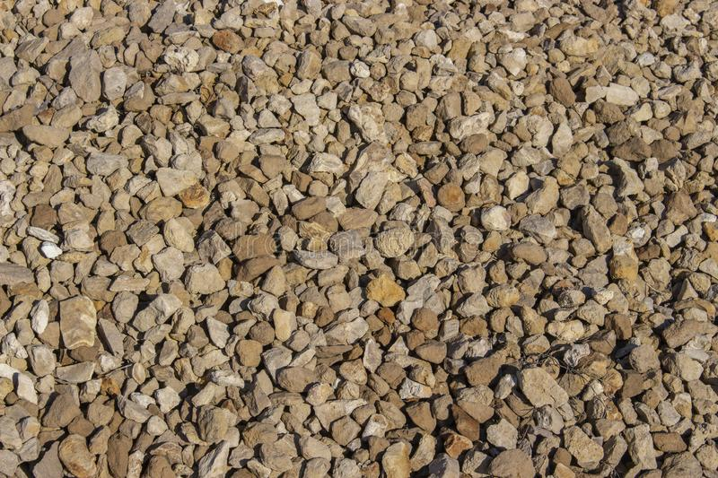 Yellow cobblestone gravel stones boulders pebbles texture background close-up. Material for repair and road construction stock photography