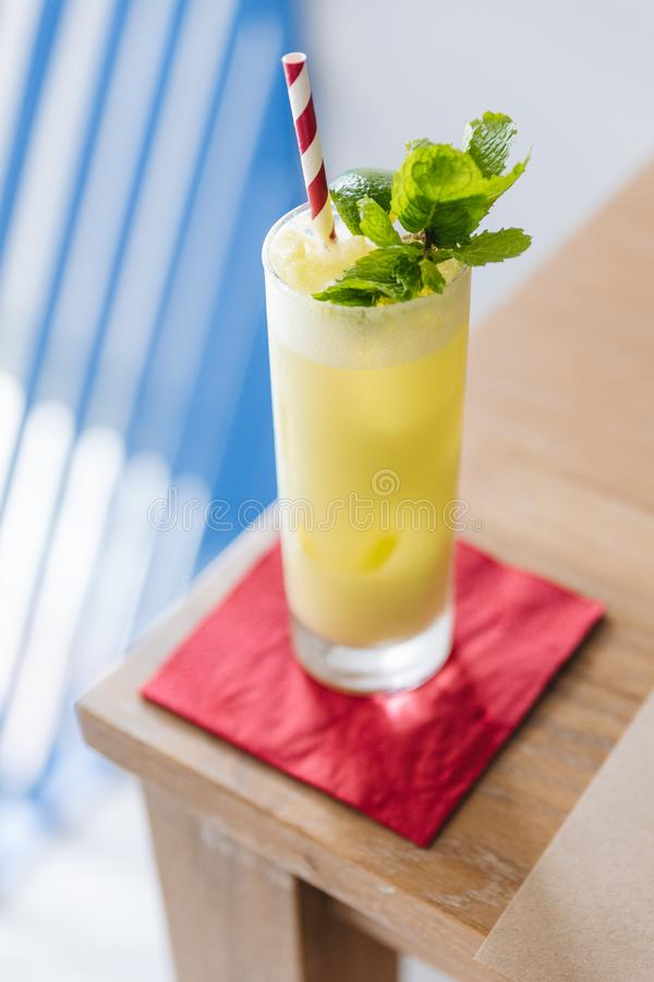 Yellow cocktail with soda bubble topping with mint leaves and slice of lime with red and with strip straw on red napkin royalty free stock photography