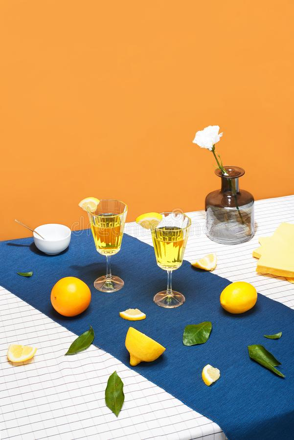 Yellow cocktails with fruits on the orange background on the restaurant table with blue tablecloth. Still life with glass. Summer royalty free stock photo