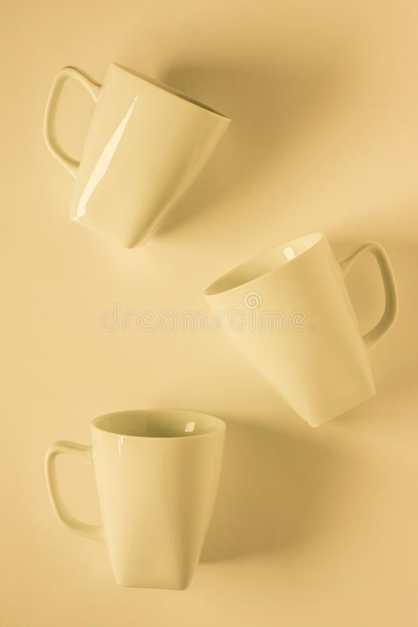 3 yellow coffee mugs on yellowish background scattered with empty copy space. 3 monochromatic yellow coffee mugs scattered on yellow background with blank empty royalty free stock image