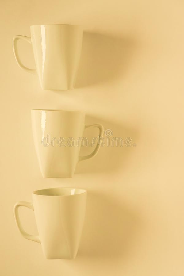 3 yellow coffee mugs on yellowish background in a vertical row, empty copy space. 3 monochromatic yellow coffee mugs lined up in a row on yellow background with royalty free stock photography