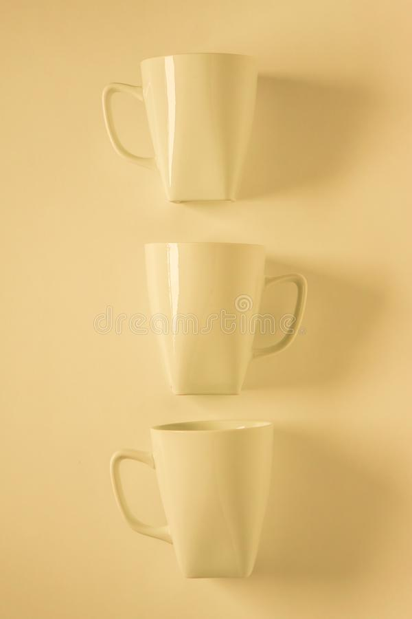3 yellow coffee mugs on yellowish background in a vertical row, empty copy space. 3 monochromatic yellow coffee mugs lined up in a row on yellow background with stock photo