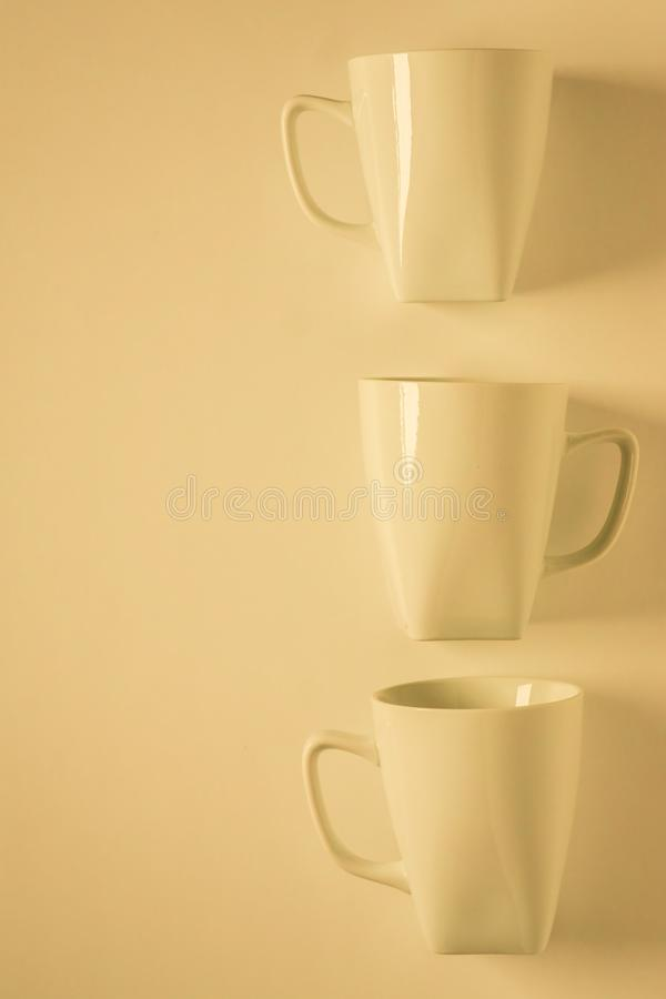 3 yellow coffee mugs on yellowish background in a vertical row, empty copy space. 3 monochromatic yellow coffee mugs lined up in a row on yellow background with royalty free stock image